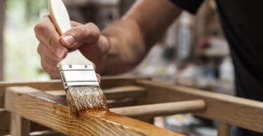 brush in hand painting garden furniture with varnish