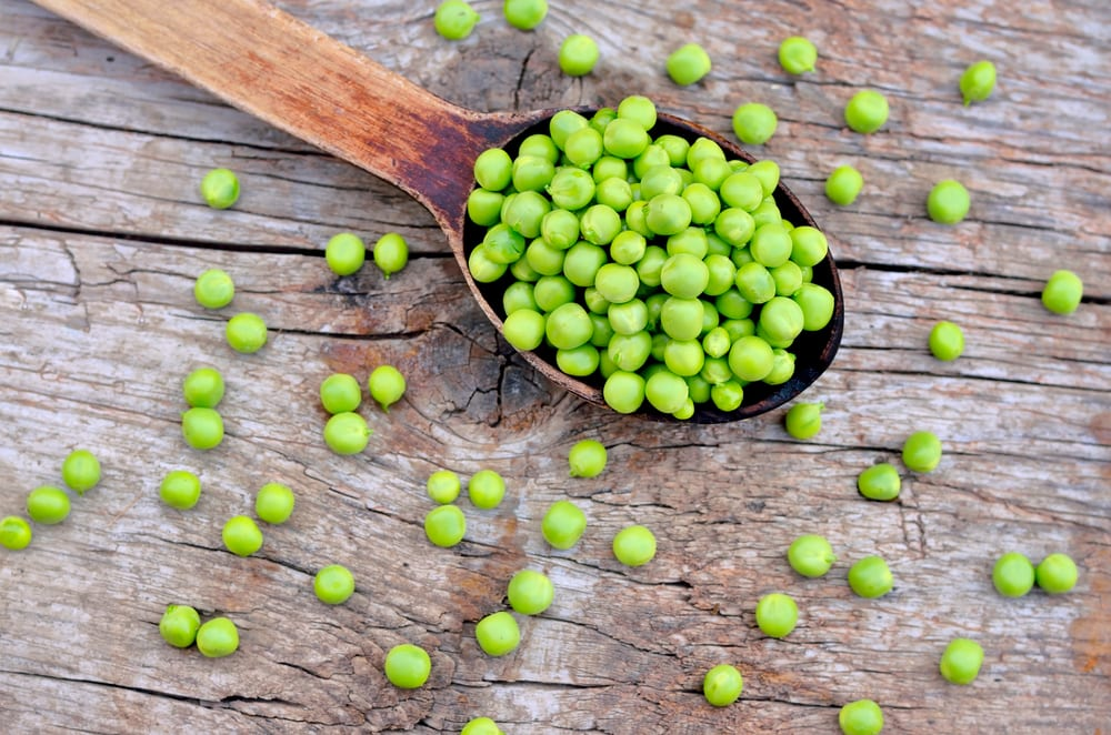 Green peas sat on a wooden spoon