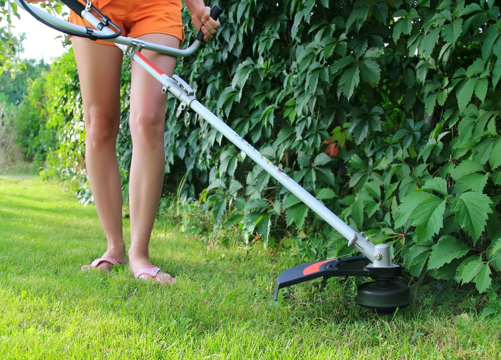 young woman mowing grass with a trimmer