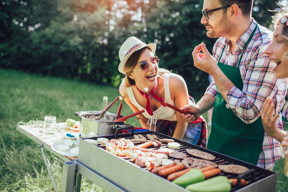 Young friends having fun grilling meat enjoying barbecue party
