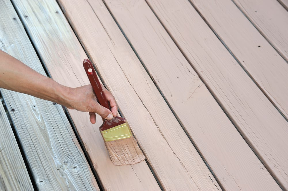 handyman painting timber deck with pink paint
