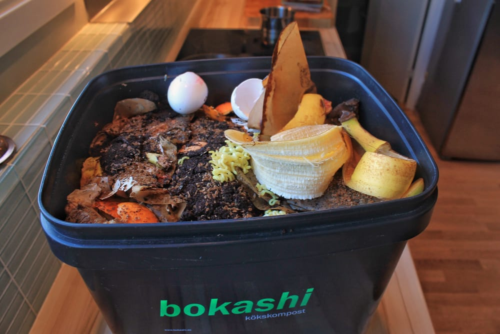A bucket on a kitchen top filled with bokashi