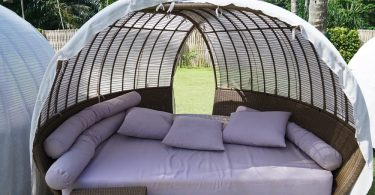 a daybed with garden in the background