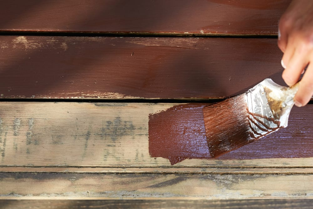 a garden deck being painted brown