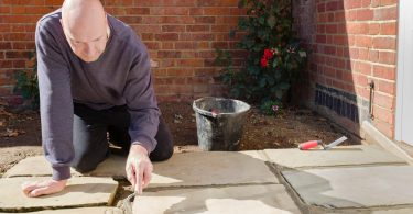 builder outdoors grouting a patio