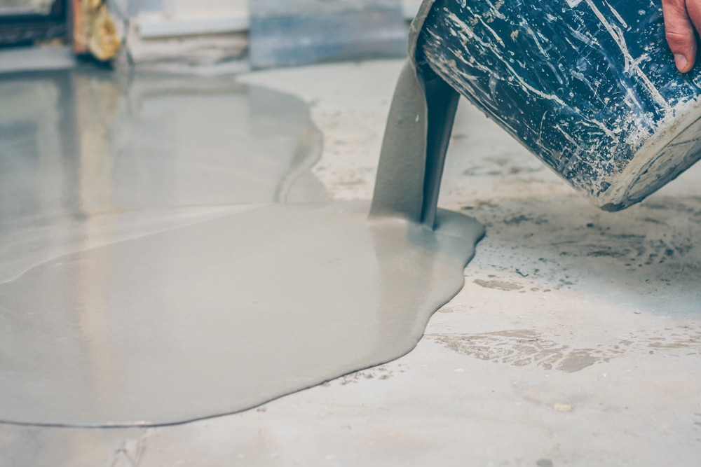 grey paint being poured on a garage floor
