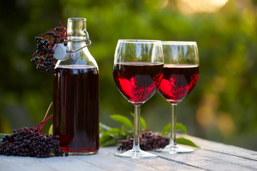 Glasses of elderberry wine on a wooden table