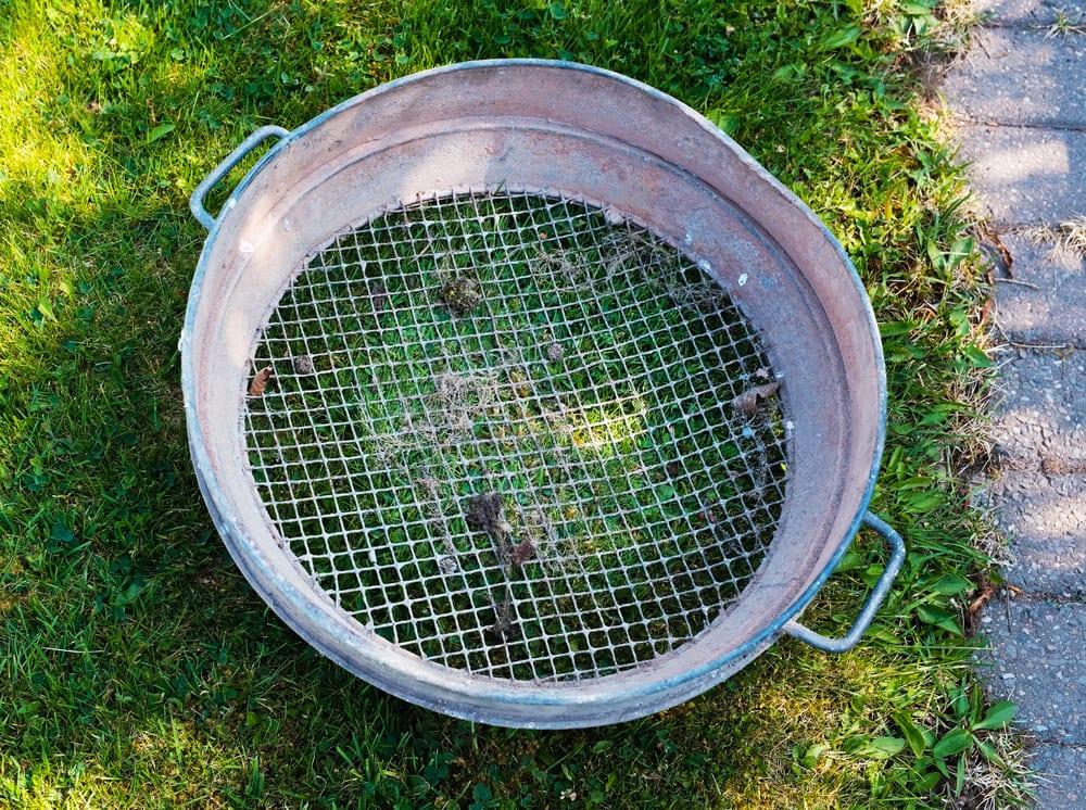 an old metal garden sieve sat on a lawn